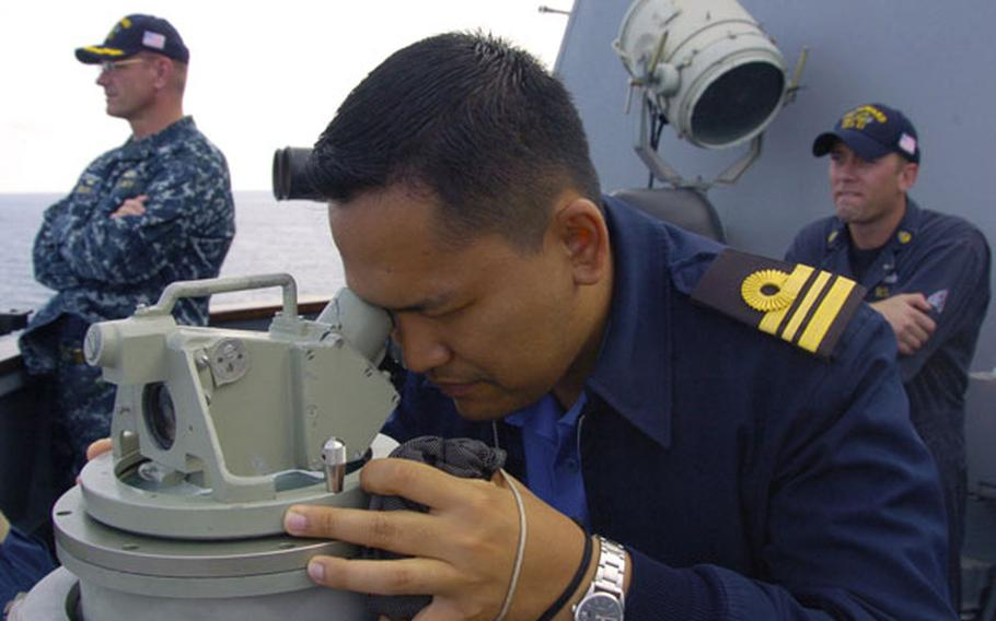 Royal Malaysian Navy Lt. Cmdr. Emmry Shahril peers at a ship formation aboard USS Howard during a bilateral exercise in the South China Sea on June 13. Recent incidents between Chinese vessels and other nations in the sea, which China claims most of as its sovereign territory, have led Southeast Asian nations to seek closer ties with the U.S. Navy.