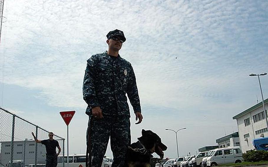 Petty Officer 2nd Class Kojiro Thomas and his military working dog, Asta, train at Sasebo Naval Base. Seaman Alex Monce observes.