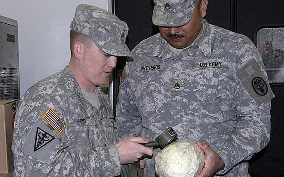 Sgt. Joshua Jones, left, a food inspector, and Staff Sgt. Fernando Ontiveros, radiation monitoring coordinator, test a head of lettuce for surface radiation during a routine inspection in March.