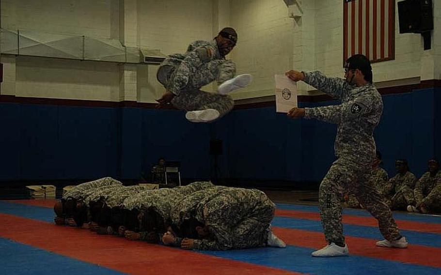 Spc. Michael Boney jumps over fellow members of the 2nd Infantry Division's Tae Kwon Do Demonstration Team to kick apart a board being held by Pfc. Clifford Labowsky during a performance Aug. 3, 2011, at Camp Red Cloud in South Korea. The team does about 15 demonstrations a year.