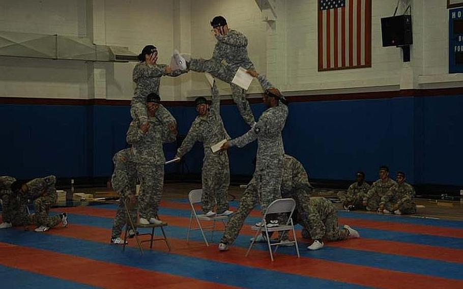 Korean Pfc. Cho Jin-hee, center, breaks board after launching himself into the air off fellow 2nd Infantry Division Tae Kwon Do Demonstration Team members Aug. 3, 2011, at Camp Red Cloud in South Korea.