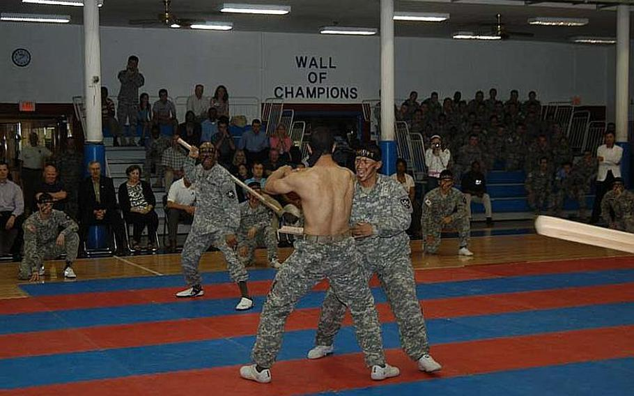 Pfc. Christopher Brown, shirtless, is struck across the midsection by a piece of wood swung by Pfc. Marjany Bolling during a 2nd Infantry Division Tae Kwon Do Demonstration Team performance Aug. 3, 2011, at Camp Red Cloud in South Korea.