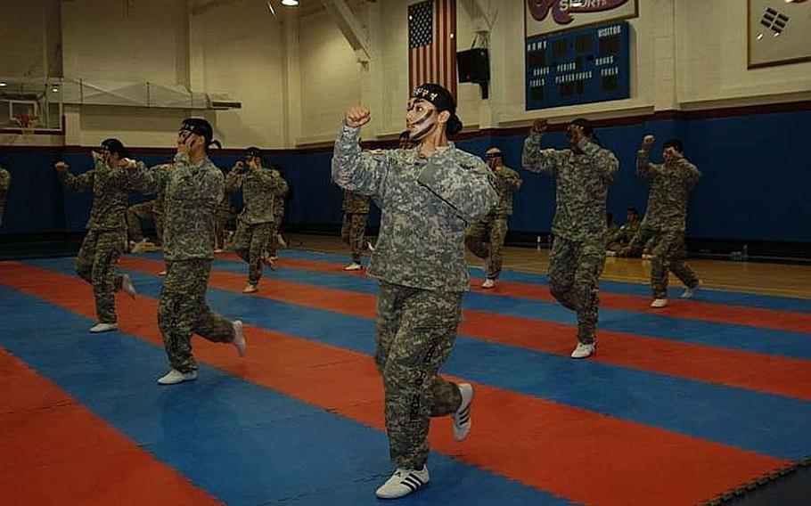 Pfc. Arianna Rendon, center, and the rest of the 2nd Infantry Division Tae Kwon Do Demonstration Team show off some moves Aug. 3, 2011, during a performance at Camp Red Cloud in South Korea.