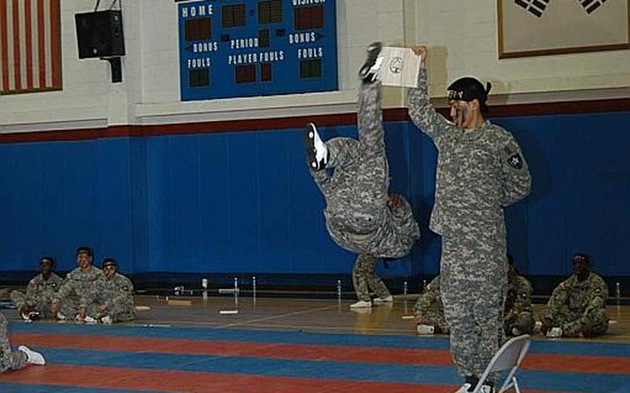 Pfc. Christopher Brown delivers a flip-kick to a board being held aloft during a performance Aug. 3, 2011, by the 2nd Infantry Division's Tae Kwon Do Demonstration Team in South Korea.