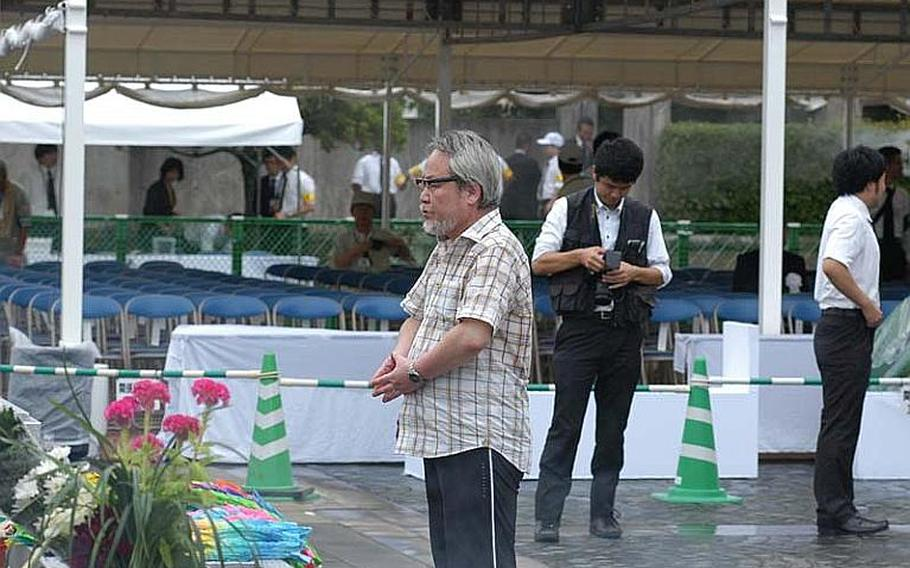 A man prays for the victims of the 1945 atomic bombing of Nagasaki before the iconic Peace Statue prior to Tuesday's ceremony.