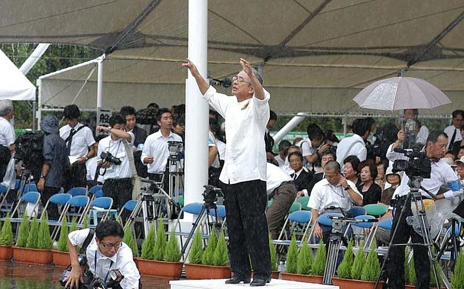 A conductor leads his vocal choir despite the driving rain prior to Tuesday's ceremony.