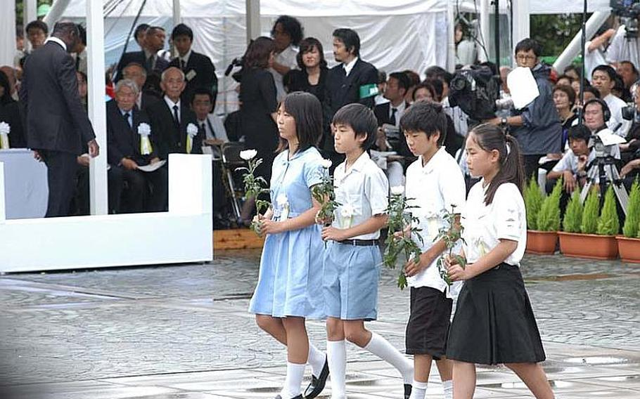 Japanese children prepare to lay flowers before the Peace Statue during Tuesday's ceremony.