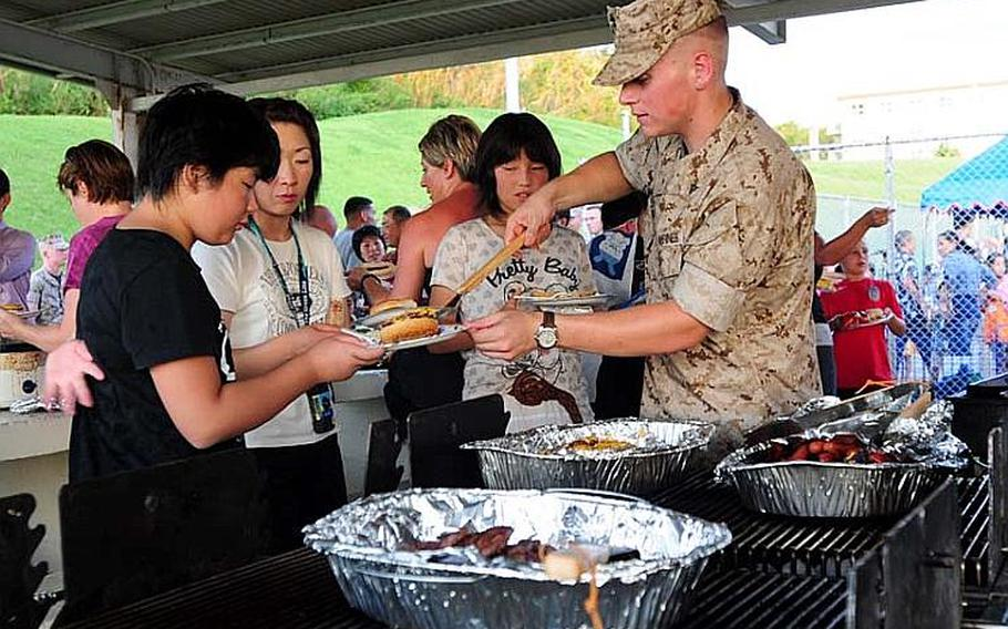 Lance Cpl. Mark Massone, serves up a hamburger to one of the 25 school children from Oshima District, Kesennuma City, Miyagi Prefecture. Their town was heavily damaged in the March 11 East Japan Great Earthquake and they visited Okinawa as part of a four-day cultural exchange/homestay program sponsored by Marine Corps Bases Japan.