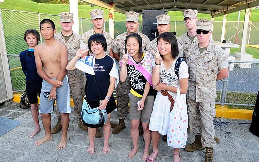 Marines pose with school children who visited Okinawa as part of a four-day cultural exchange/homestay program sponsored by Marine Corps Base Japan. The children are from Oshima District, Kesennuma City, Miyagi Prefecture and their town was heavily damaged in the March 11 East Japan Great Earthquake.