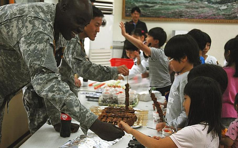 """Spc. John Anderson """"sells"""" a meat kebab to a Taesongdong Elementary School student during the school's market day, when students practice buying and selling goods in English. U.S. troops stationed at the Joint Security Area visit the school once or twice a week to help teach English."""