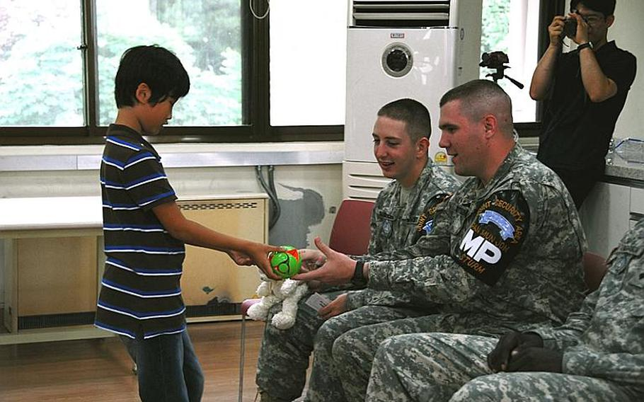"""Spc. Joshua Sturn, right, """"buys"""" a toy from a Taesongdong Elementary School student during the school's market day, when students practice buying and selling items in English. To his left is Pvt. Bradley Chamberlain. Both are stationed in the Joint Security Area."""