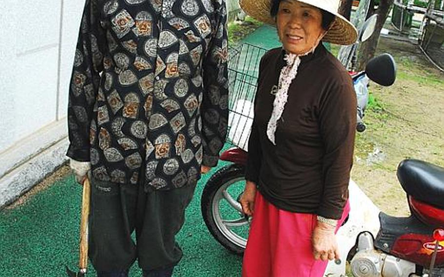 Kim Dong-gyu, left, and his wife take a break during a day of farming in Taesongdong. Kim, 72 and a lifelong resident of Taesongdong, said the village was terrorized by Chinese troops during the Korean War, and said he worries more about losing his land someday than a North Korean attack.