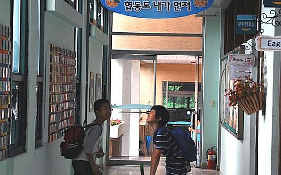 Two students joke in the halls of Taesongdong Elementary School as they leave the building at the end of the day.