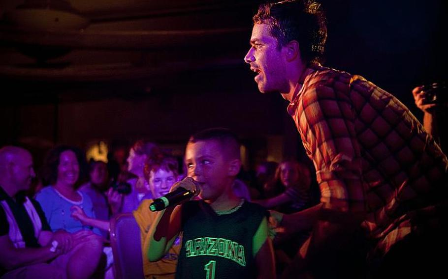 Past American Idol contestant Colin Benward shares the microphone with a young fan Wednesday night during a performance at Yokota Air Base.