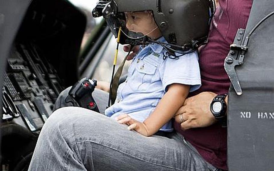 A father and son enjoy a moment in the cockpit of a UH-60 Black Hawk during the annual Japanese-American Friendship Festival at Yokota Air Base, Japan, on Aug. 20, 2011.