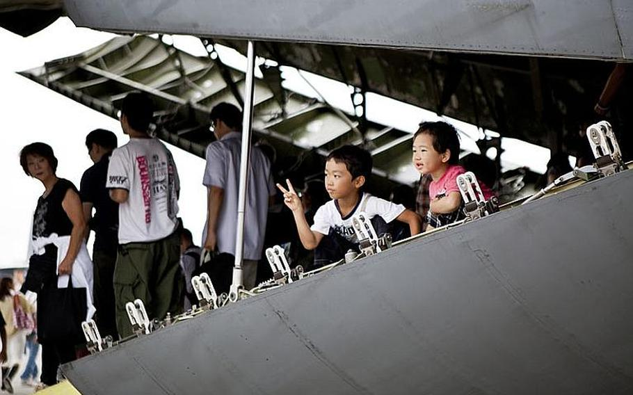 Two children pose for a photo inside a C-5 Galaxy transport aircraft during the annual Japanese-American Friendship Festival at Yokota Air Base, Japan, on Aug. 20, 2011.