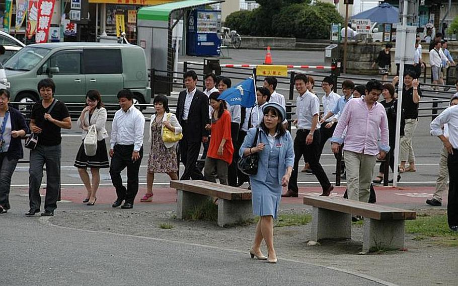 Some of the first tourists to return to Matsushima, Japan, after the March earthquake and tsunami follow a tour group leader on Aug. 24, 2011.