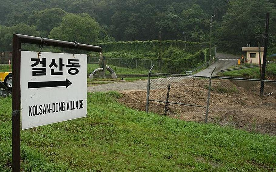 A sign on Camp Casey in South Korea points the way out Gate 11 and up a hill to Golsandong Village, where about 130 are essentially landlocked between the base and the nearby mountains. Because of that, village residents are issued passes that allow them 24-access to cut through Camp Casey going to or from the outside world. Korean words are sometimes spelled different ways when translated into English, thus accounting for the alternate names of the village.