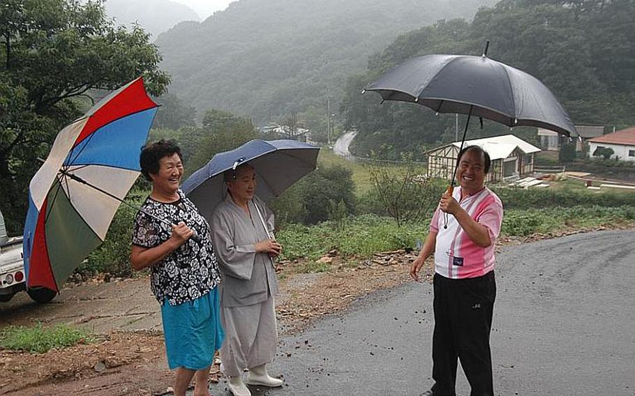 Kim Kwang-su, right, the mayor of Golsandong in South Korea, chats with village residents Yun Gan-nan, left, and Jihyun, center, during a chance meeting recently. The village has a unique relationship with Camp Casey, an adjacent U.S. military base. Residents fear when the U.S. base is vacated as planned in the years ahead, the charm and character of the village will be ruined as the Camp Casey property is developed.