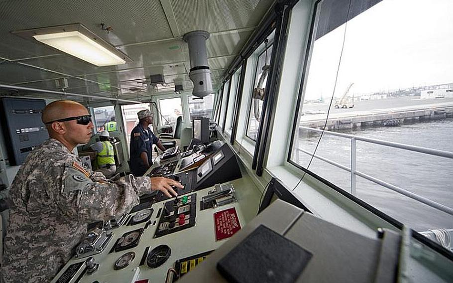 Chief Warrant Officer 2  Matthew Jones, from the 97th Transportation Co. in Fort Eustis, Va., checks the controls of the Army's Land Craft Utility 2000 at Yokohama North Dock on Wednesday.