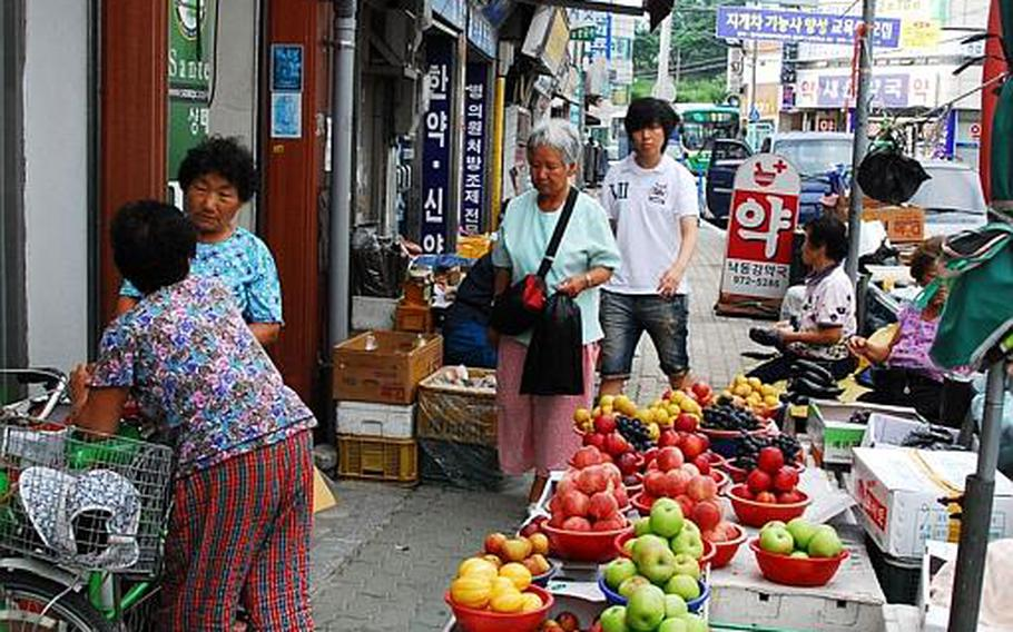 Women talk in front of a fruit stand on a busy street in the heart of Waegwan in South Korea. Concerns over possible exposure to Agent Orange, has led the South Korean government to conduct a health study on residents living near Camp Carroll.