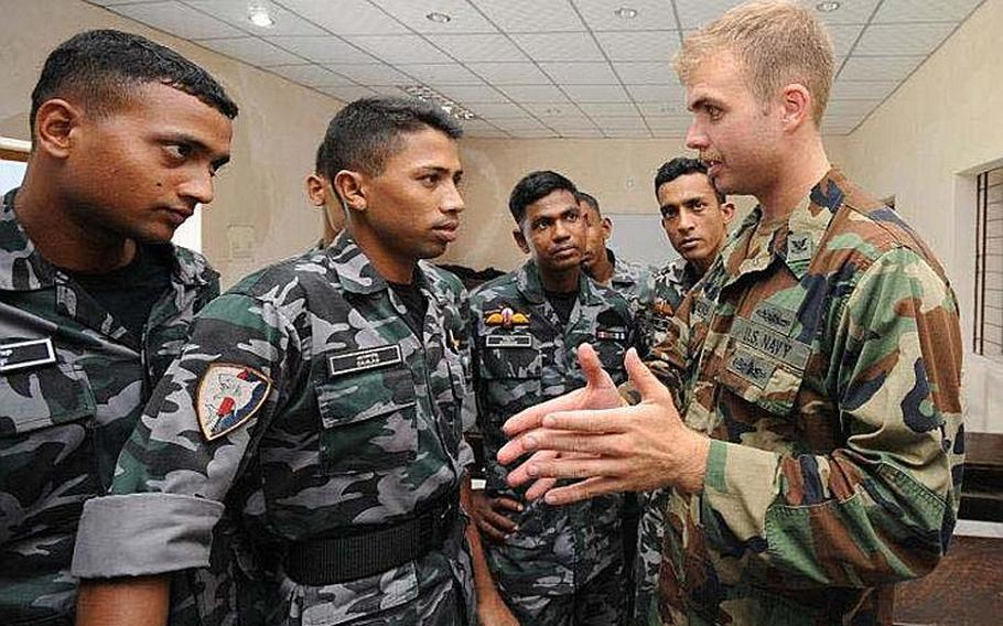 Engineman 2nd Class Benjamin Clemens (right), attached to Riverine Squadron (RIVRON) One, discuses riverine operations concepts with Bangladesh Navy sailors Monday during Cooperation Afloat Readiness and Training (CARAT) Bangladesh 2011. CARAT 2011 is a series of bilateral exercises held annually in Southeast Asia to strengthen relationships and enhance force readiness.