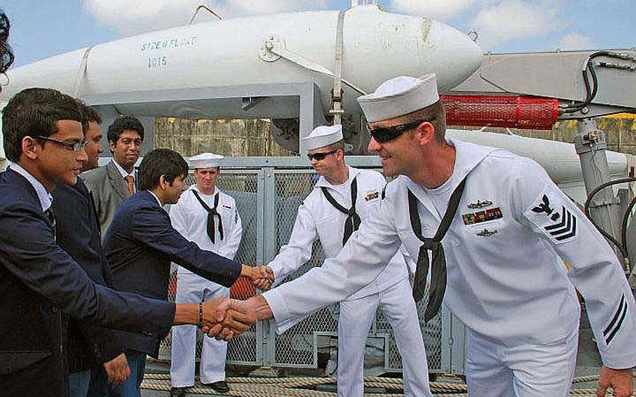 Mineman 1st Class Ben Hall and Mineman 3rd Class Zach Abel greet high school students from Chittagong Grammar School mONDAY during a ship tour of the Sasebo-based USS Defender, during Cooperation Afloat Readiness and Training (CARAT) Bangladesh 2011. CARAT 2011 is a series of bilateral exercises held annually in Southeast Asia to strengthen relationships and enhance force readiness.