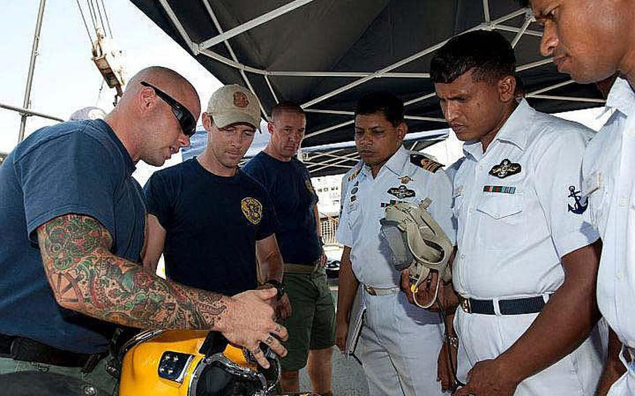 Petty Officer 2nd Class Taylor Nevius, a Navy diver from Mobile Diving and Salvage Unit 1, explains a KM-37 Deep Sea Diving Helmet to divers from the Bangladesh navy aboard USNS Safeguard. Safeguard is in Chittagong for Cooperation Afloat Readiness and Training (CARAT) Bangladesh 2011. CARAT is a series of bilateral exercises held annually in Southeast Asia to strengthen relationships and enhance force readiness. CARAT Bangladesh 2011 marks the first time the Bangladesh navy has participated in the exercise series.