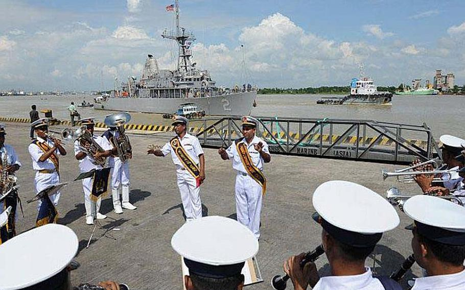 The Bangladesh navy band performs on the pier Sept. 18, 2011, as the Sasebo-based mine countermeasure ship, USS Defender, maneuvers to arrive in Chittagong. The USS Defender is in Chittagong for Cooperation Afloat Readiness and Training (CARAT) Bangladesh 2011. CARAT is a series of bilateral exercises held annually in Southeast Asia to strengthen relationships and enhance force readiness. CARAT Bangladesh 2011 marks the first time the Bangladesh navy has participated in the exercise series.