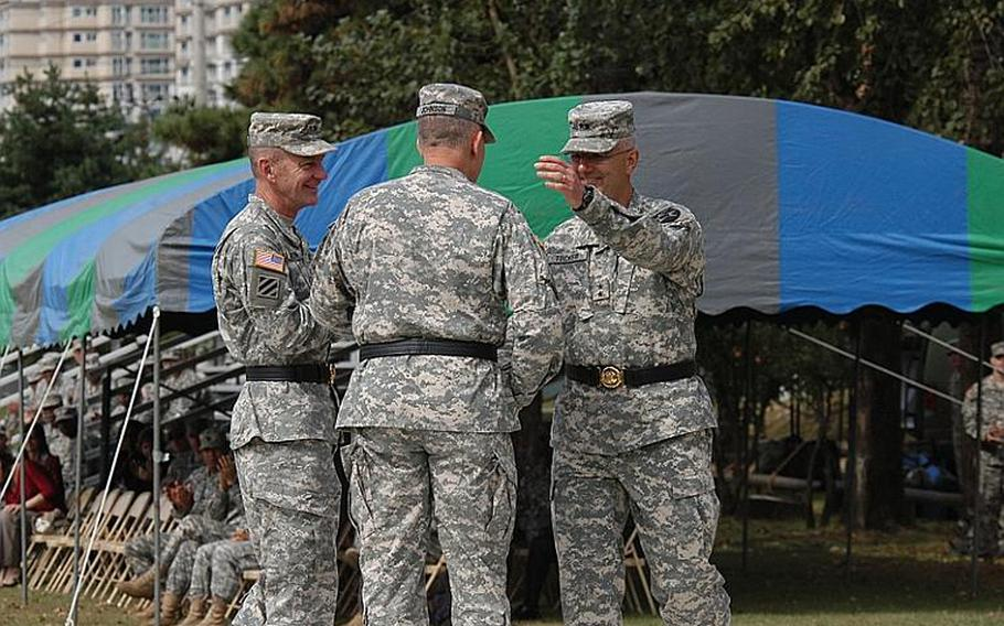 Eighth Army commander Lt. Gen. John Johnson, center, shakes hands with outgoing 2nd Infantry commander Maj. Gen. Michael Tucker, right, at a change of command ceremony Tuesday at Camp Casey in South Korea. Maj. Gen. Edward Cardon, left, assumed command of the division at the ceremony.
