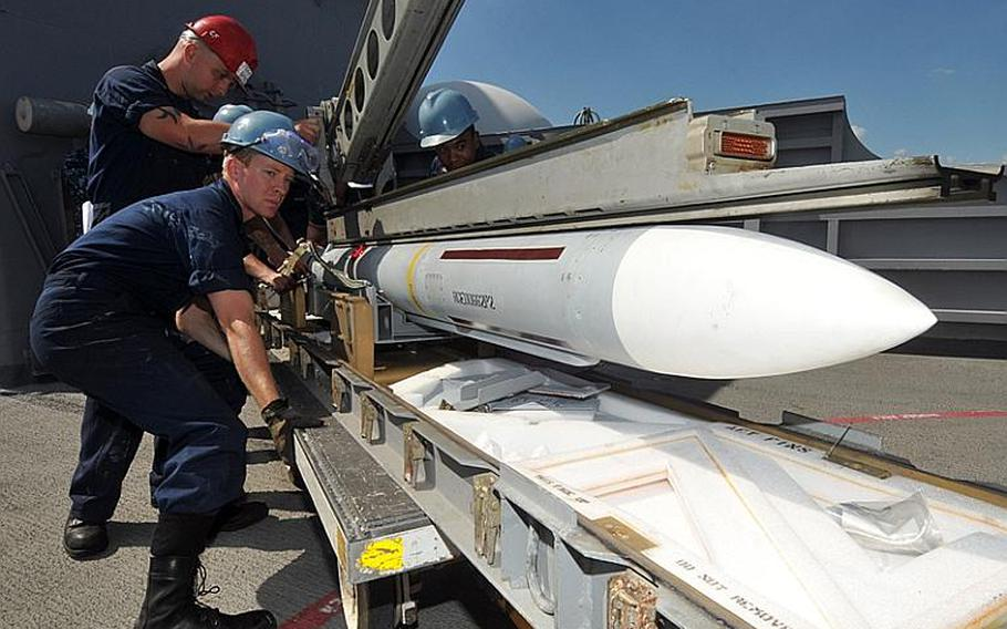 Fire Controlman 3rd Class Justin Clark (middle), Fire Controlman 2nd Class Richard Todd (left) and Fire Controlman 2nd Class Victor Masterson prepare to load a NATO Sea Sparrow missile in a launcher aboard the forward deployed amphibious assault ship USS Essex Friday. The Essex is currently underway for a patrol of the western Pacific.