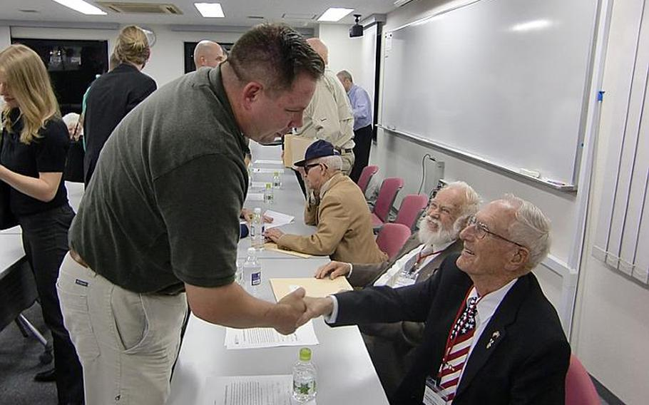 Army Col. Jeff Oppenheim, left, shakes hands with 91-year-old Harold A. Bergbower, following a lecture at Temple University on Oct. 17, 2011, in Tokyo. Bergbower and six other WWII POWs are touring Japan this week this week seeking closure to the brutal treatment they endured while held captive.