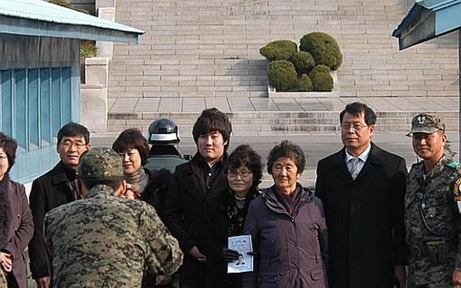 Members of the family of Cpl. Jang Myunk-ki pose for photos at the Demilitarized Zone in Korea as a North Korean soldier looks on from the other side of the Military Demarcation Line. The family was at the DMZ on Nov. 23, 2011, for a ceremony marking the 27th anniversary of a firefight in which Jang, a Korean augmentee to the U.S. Army, was killed.