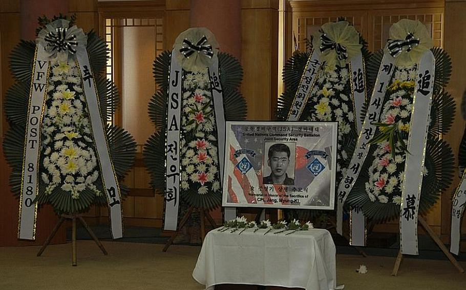 Flowers surround a photo of Cpl. Jang Myung-ki after a ceremony Nov. 23, 2011, at Korea's Demilitarized Zone marking the 27th anniversary of a firefight there in which Jang was killed. Jang was a Korean augmentee to the U.S. Army.