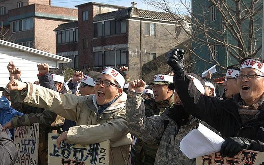 A group of about 50 security guards chant in protest Dec. 1, 2011, across the street from Camp Red Cloud in Uijeongbu. The guards are upset that the company that the week of Nov. 28 took over security for U.S. Army installations in South Korea will only hire them if they accept less pay and longer hours than they worked for the company that formally held the security contract.