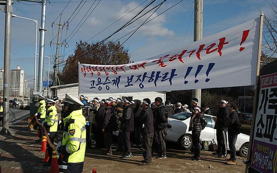 South Korean police standby Dec. 1, 2011, near a group of security guards protesting across the street from Camp Red Cloud in Uijeongbu. The guards are upset that the company that the week of Nov. 28 took over security for U.S. Army installations in South Korea will only hire them if they accept less pay and longer hours than they worked for the company that formally held the security contract.