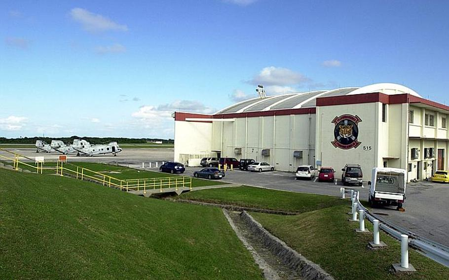Marine Corps Sea Knight helicopters sit near a hangar on the Futenma air station on Dec. 2, 2011.