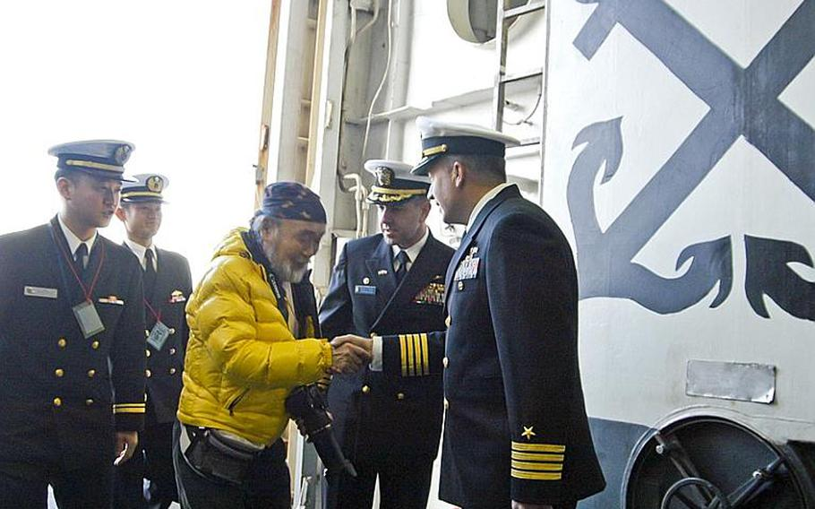 Shima Takashi, in yellow, is greeted Dec. 13, 2011, by Capt. David Fluker, center, skipper of the Wasp class multipurpose amphibious assault ship USS Essex, and Capt. Daniel Dusek, right, the ship's executive officer, as he arrives at the ship to present his most recent work for display. The 68-year-old  from Wakayama prefecture painted the Essex in elaborate detail to thank the U.S. military and the ship&'s crew for their participation in Operation Tomodachi.