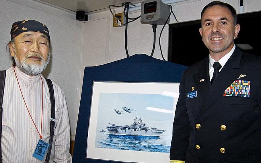 Shima Takashi, left, a 68-year-old renowned painter from Wakayama prefecture, presents a painting he made of the Wasp class multipurpose amphibious assault ship USS Essex to its skipper, Capt. David Fluker, right, Tuesday morning during a small ceremony in the captain's quarters. Takashi painted the Essex in elaborate detail to thank the U.S. military and the ship's crew for their participation in Operation Tomodachi.