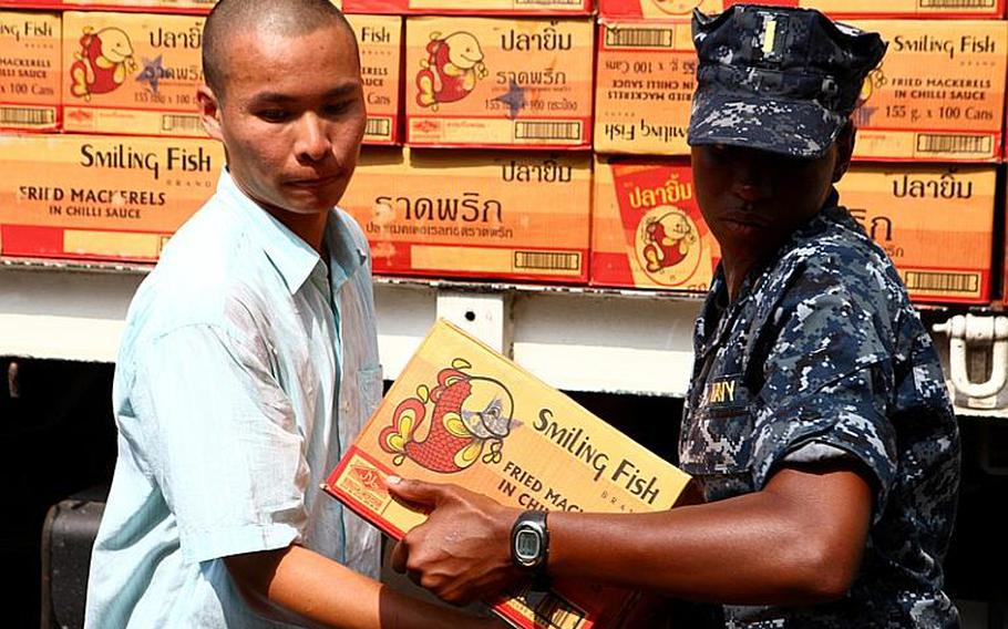 Ensign Elisha Dotson, combat information officer from the Arleigh Burke-class guided missile destroyer USS Lassen, helps a local Thai unload supplies off a truck in Bangkok on Nov. 18. Sailors from the Lassen visited the Thai Red Cross Society distribution center and helped locals load, unload and distribute supplies. In coordination with the U.S. Embassy in Bangkok and the Royal Government of Thailand, U.S. Pacific Command directed theater service components to conduct joint operations in support of disaster assessment and relief operations in Thailand. The III MEF Flood Relief Command Element consisting of joint service members will provide assessment for additional U.S. forces to assist the Royal Government of Thailand.