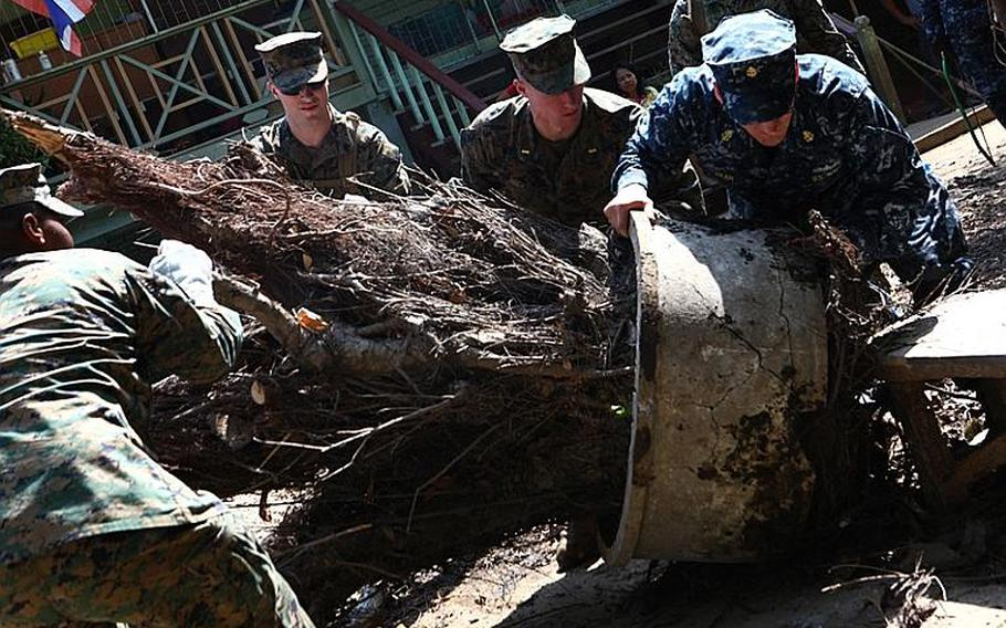 U.S. service members remove fallen debris at the Sanamchai School in Lop Buri on Nov. 20, 2011. Joint U.S. forces came together to assist the Royal Thai Army Special Warfare College clean community facilities. U.S. forces continue to support the Royal Government of Thailand in their flood relief efforts.