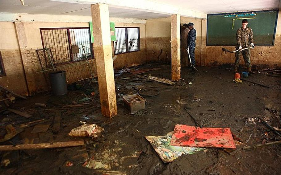 Satellite operator Lance Cpl. Christopher Brown, right, and Petty Officer 2nd Class Charlie Harper, a gunner's mate, gain perspective on the effects left from flood water as they help clean up the Sanamchai School in Lop Buri on Nov. 20, 2011. Brown, an Atkinson, N.H. native, is with the III Marine Expeditionary Force Flood Relied Command Element. Harper, a Spokane, Wash. native, is with the Arleigh Burke-class guided missile destroyer USS Lassen. Joint U.S. forces came together to assist the Royal Thai Army Special Warfare College clean community facilities. U.S. forces continue to support the Royal Government of Thailand in their flood relief efforts.