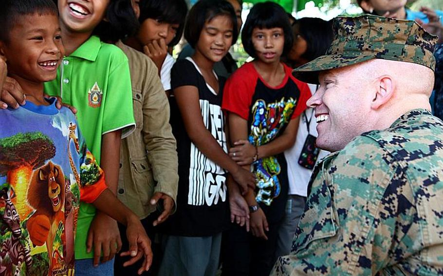 Maj. Jason Wintermute, an anti-terrorism force protection officer, interacts with local children in Lop Buri on Nov. 20. Wintermute, a West-Chester, Penn. native, is with the III Marine Expeditionary Force Flood Relief Command Element. Joint U.S. forces came together to assist the Royal Thai Army Special Warfare College clean community facilities. U.S. forces continue to support the Royal Government of Thailand in their flood relief efforts.
