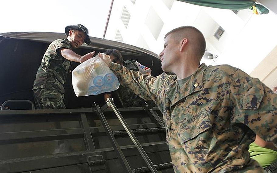 U.S. Marine Maj. Eric Mattson helps load food, water and medical supplies on the Royal Thai  Army truck that was sent out to the flood victims in Bangkok, Thailand, Nov. 19, 2011.  In coordination with the U.S. Embassy in Bangkok and the Royal Government of Thailand, U.S.  Pacific Command directed theater service components to conduct joint operations in support of disaster assessment and relief  operations in Thailand. The III Marine Expeditionary Force Flood Relief Command Element consisting of Marines and sailors from Okinawa, Japan will provide command and control for possible additional U.S. forces to assist the Royal Government of Thailand.