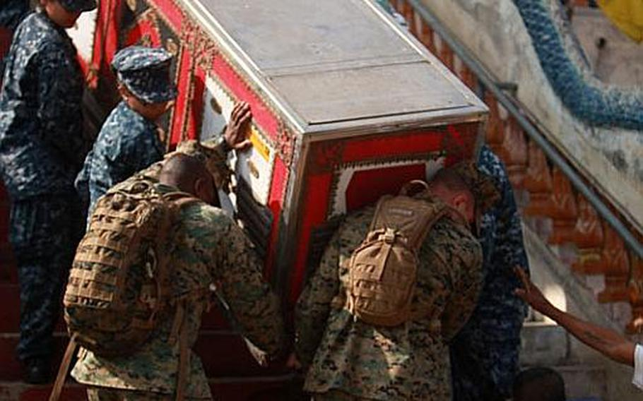 Marines attached to III Marine Expeditionary Force Flood Relief Command Element, and sailors from the USS Lassen work together to clear damaged items from a temple at Saban Bridge that was affected by the recent flooding on Nov. 21. In coordination with the U.S. Embassy in Bangkok and the Royal Government of Thailand, the U.S. Pacific Command directed theater service components to conduct joint operations in support of disaster assessment and relief operations in Thailand. III Marine Expeditionary Force sent a Flood Relief Command Element consisting of Marines and sailors from Okinawa, Japan which provide command and control for additional U.S. forces to assist the Government of Thailand.
