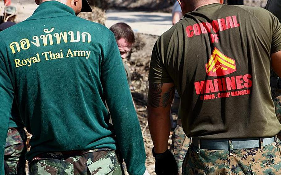 Cpl. Wyethpaul N. Yadao stands alongside a member of the Royal Thai Army while removing debris and opening relief distribution sites in Ayutthaya on Nov. 23, 2011. Yadao, a Kailua Kona, Hawaii, native, is attached to the III Marine Expeditionary Force Flood Relief Command Element. Service members continue to support the Royal Government of Thailand in their flood relief efforts.