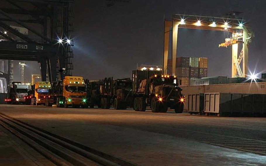 A line of 7-ton tactical vehicle replacements and flat-bed semi-trucks loaded with water pumps, hose reels, and other equipment are staged on the pier in Laem Chabang on Nov. 29, 2011. The equipment will be used in flood recovery efforts by a detachment of Marines with 9th Engineer Support Battalion who will be working with the Royal Thai Air Force to conduct water removal operations at the Don Mueang Airfield in Bangkok. U.S. forces working in conjunction with III Marine Expeditionary Force Flood Relief Command Element, as well as, interagency partners continue to support and assist the Royal Government of Thailand through combined operations to provide humanitarian assistance and flood relief to the citizens of Thailand.