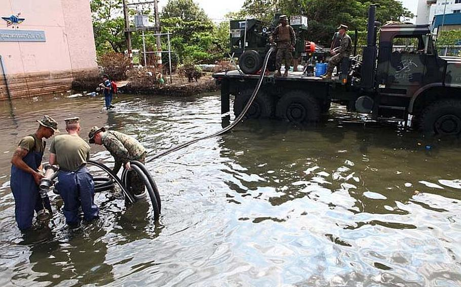 Marines with 3rd Marine Logistics Group place flood relief equipment on top of a Medium Tactical Vehicle Replacement during their relief efforts Nov. 29, 2011. In conjunction with the III Marine Expeditionary Force Flood Relief Command Element and interagency partners, servicemembers helped with flood relief efforts pertaining to the Don Mueang Airport and its facilities.