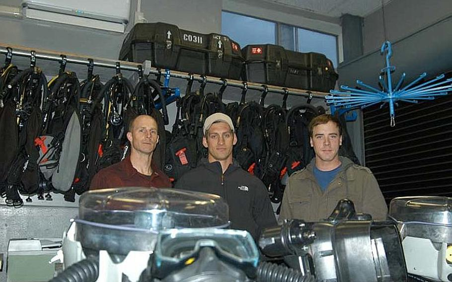 From left to right, Petty Officer 1st Class Corey Baughman, Petty Officer 1st Class Dillon Mudloff, and Petty Officer 3rd Class Adam Andryc, of Explosive Ordinance Disposal Mobile Unit 5, Detachment 51, pose in their shop with their bomb disposal gear. The trio of bomb technicians saved the life of a Japanese national while climbing Mt. Fuji on Dec. 9-12, 2011. The sailors got more than they bargained for on what turned out to be a harrowing weekend on the mountain. Baughman suffered frostbite staying on the mountain overnight with the man after he fell. Baughman's efforts helped the man fight off shock and certain death. The man was rescued the next day.