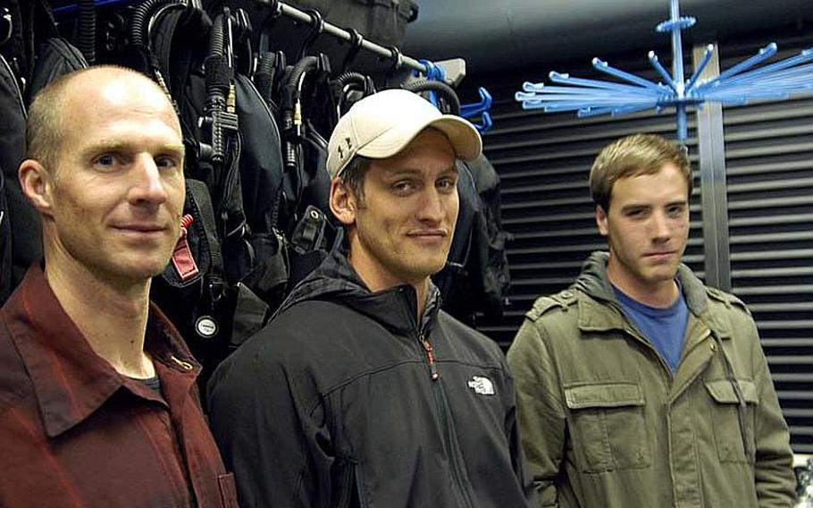 From left to right, former Petty Officer 1st Class Corey Baughman, Petty Officer 1st Class Dillon Mudloff, and Petty Officer 3rd Class Adam Andryc, of Explosive Ordnance Disposal Mobile Unit 5, Detachment 51, pose in their shop with their bomb disposal gear. The trio saved the life of a Japanese national while climbing Mt. Fuji on Dec. 9-12, 2011.